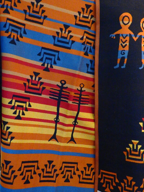 Pendleton Woolen Mills blanket designed by Lillian Pitt is an exclusive at the Friends Bookstore & Gallery. Tribal designs in bright colors are woven into the blanket.