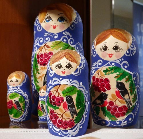 Russian nesting dolls in vibrant colors feature red-breasted birds and red berries with green leaves.