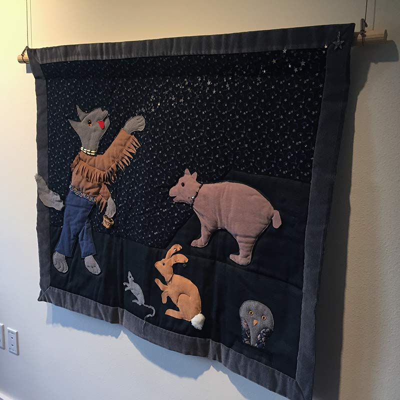 Quilt made by Pat Courtney Gold depicting the story of the coyote, bear, and rabbit from Wasco tribe
